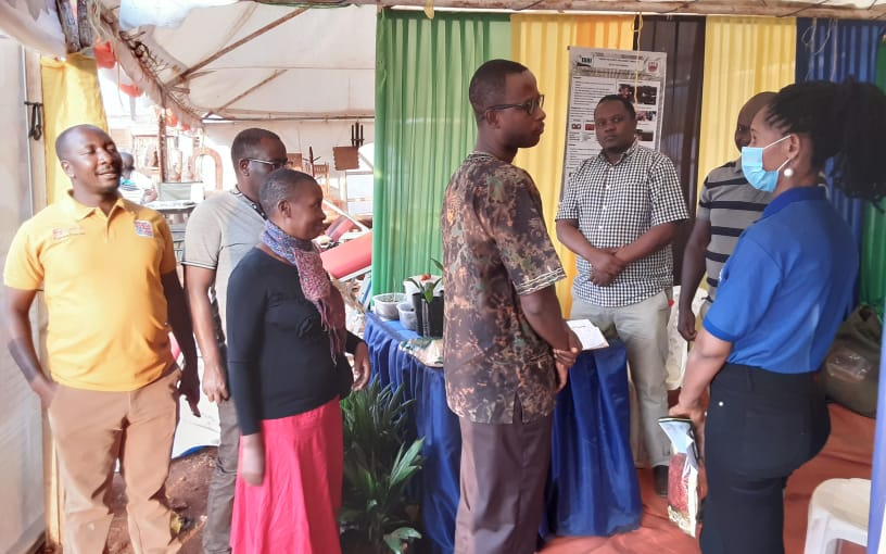 The Center Director of TARI Kihinga Research Center  Dr Filson Kagimbo giving a briefing on the investment opportunity in Oil Palm Industry to the visitor from  Tanzania  Investment Center (TIC) Ms. Latifa Kigoda at ongoing SIDO National Exhibition in Kas