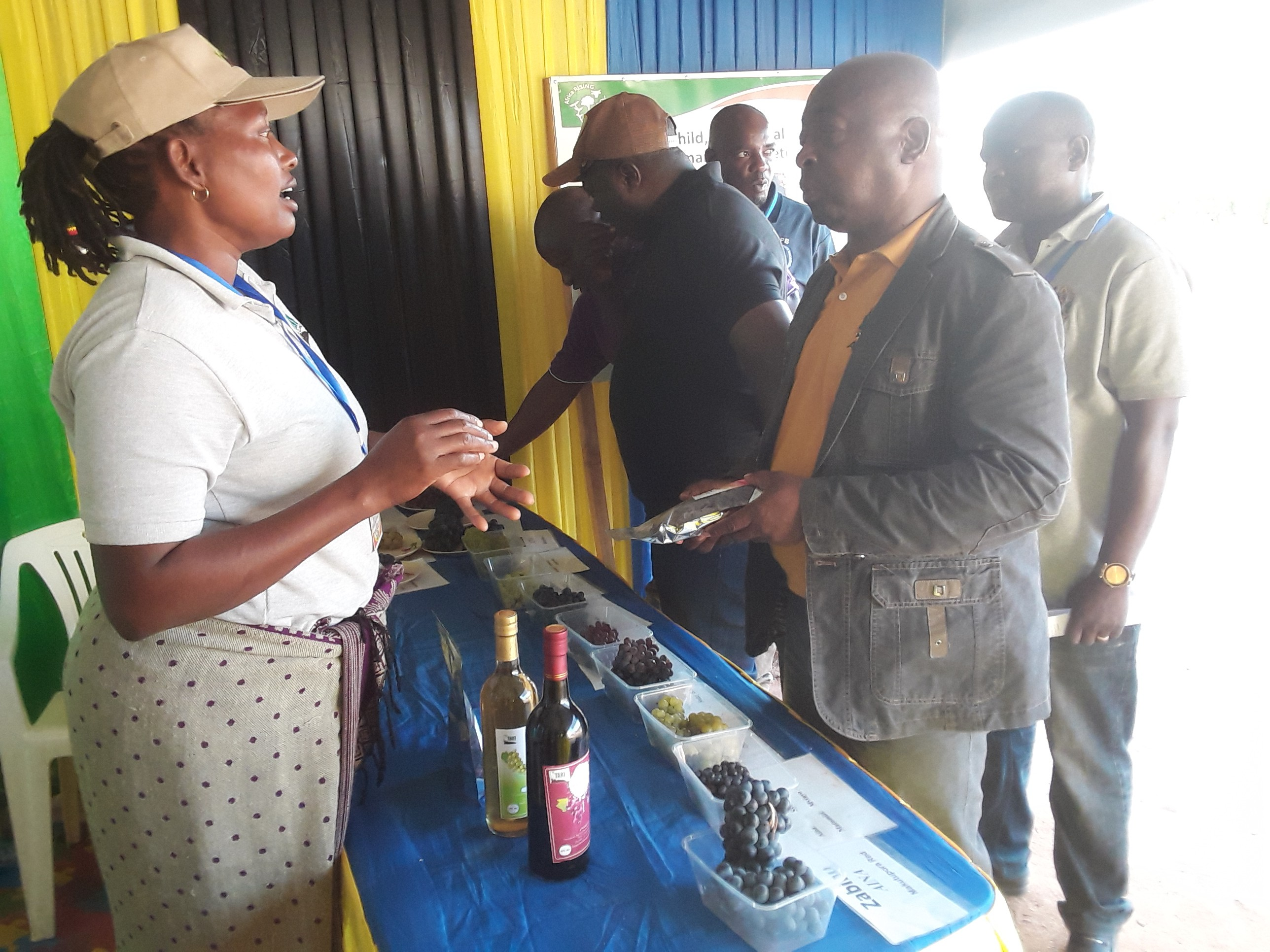 Food scientist - Felista Mpore giving explanations to the Deputy Principal Secretary -Ministry of Agriculture  Prof  Tumbo  activities done by TARI-Makutupora food processing unit during farmers festivals (Nanenane) at Nzuguni grounds Dodoma